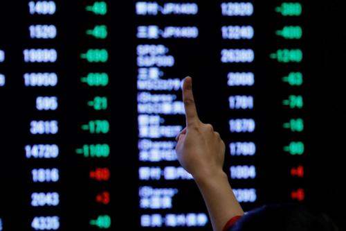 Một nhà đầu tư giơ ngón tay thể hiện sự kỳ vọng với chứng khoán Nhật Bản năm nay. Ảnh: Reuters  - japan stock 7948 1560910256 - Chứng khoán châu Á bật tăng vì kỳ vọng đàm phán Mỹ – Trung