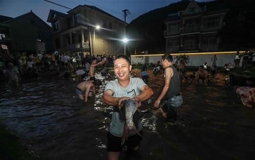 Du khách tham gia sự kiện bắt cá tại một ngôi làng ở Hàng Châu. Ảnh: Xinhua  - bat ca 7476 1568957567 - Nỗ lực thành ngôi sao kinh tế đêm của TQ